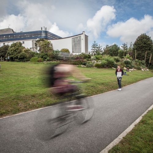 A student riding a bike on a path on Penryn Campus