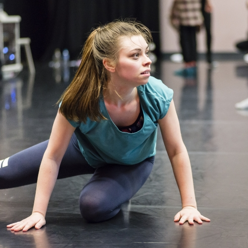 Student dancer with hands on floor and leg extended.
