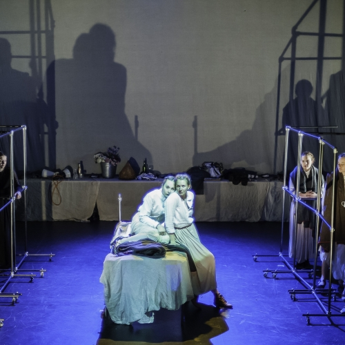 Actors sat on table on stage, back lit with blue light, large shadows on curtain behind them.