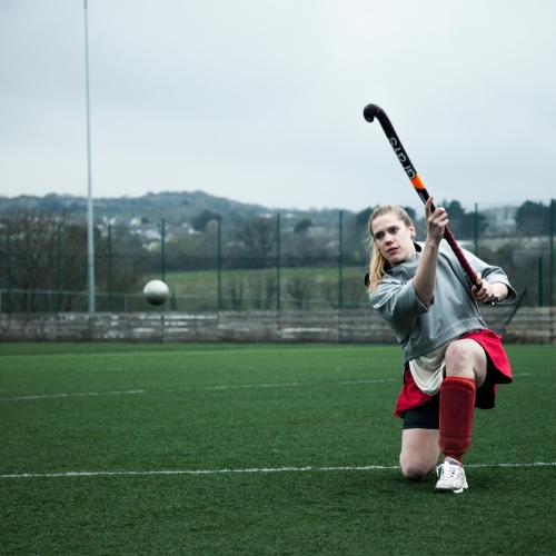 Female on knee with hockey stick in the air and the ball in mid flight.