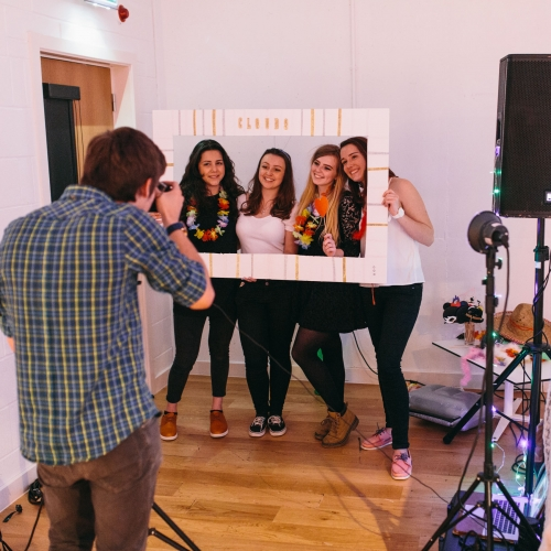 Students having photograph taken in studio holding a handmade frame to frame their faces