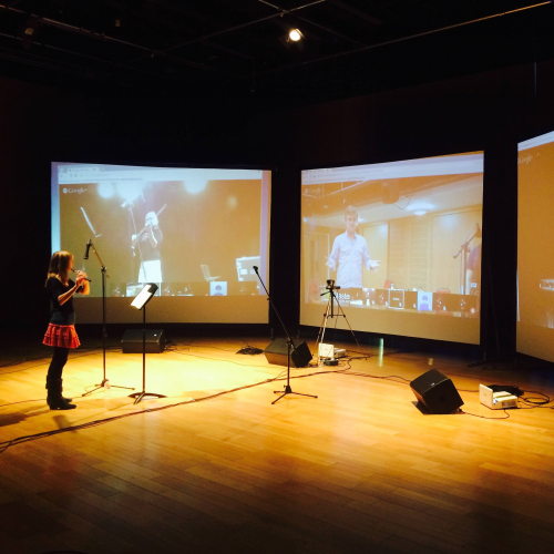 A woman playing the clarinet in front of three digital screens