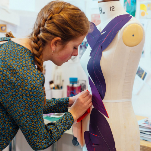 Costume Design student pinning purple fabric leaves to mannequin.