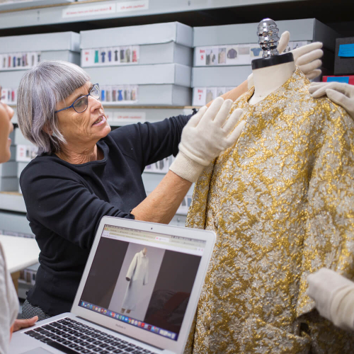 Costume Design student and lecturer examining a gold coat