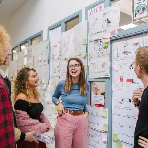 Creative advertising students discussing in front of an ideas wall.