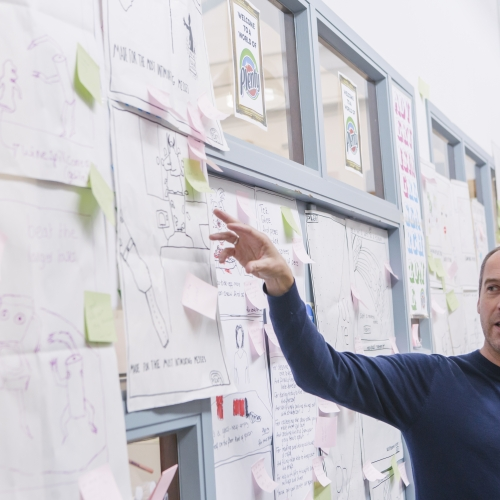 Creative advertising lecturer pointing at an ideas and notes wall.