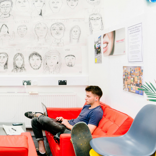 Male Creative Advertising student sitting on a red sofa at Falmouth University