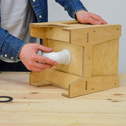 A person putting a white pipe on a wooden box