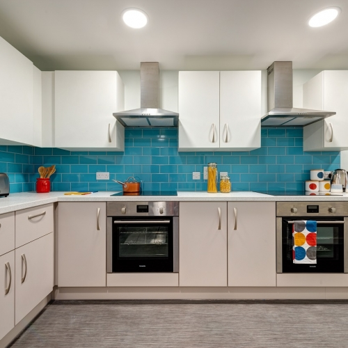 Kitchen interior with white cupboards and teal coloured tiles