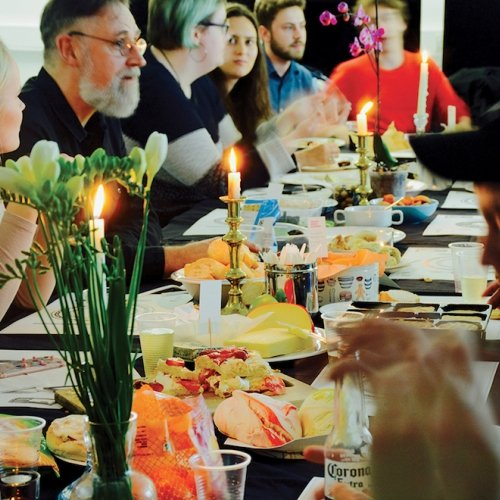 People sitting around a long table with candles