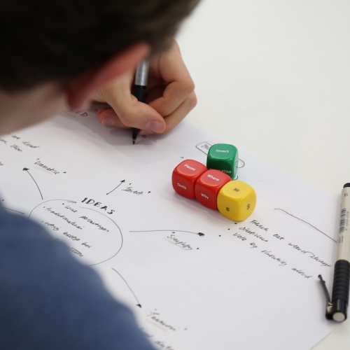 Person writing a spider diagram on a sheet of paper with dice and pen.