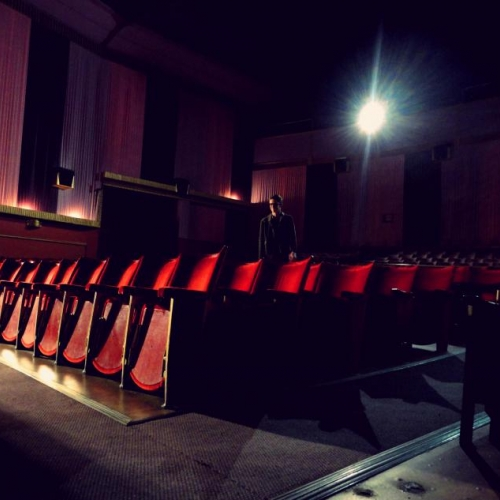 A man stood amongst red cinema seats, glare of the projector behind him.