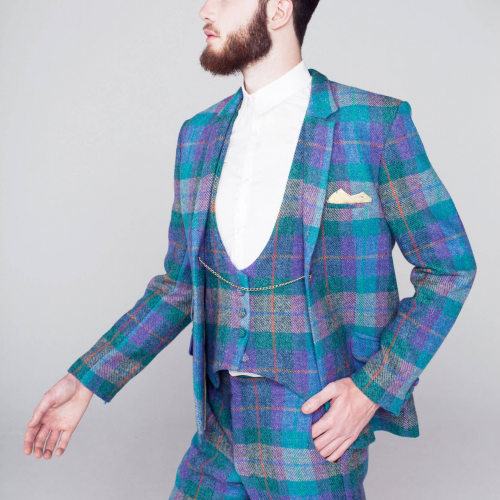 Model in tweed three piece suit in bright blues, purples and greens.