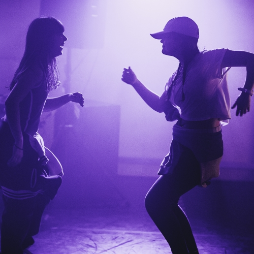 Two people dancing at a hip hop event