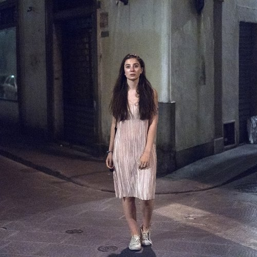 woman with long brown hair wearing a pink dress, stood on the street at night