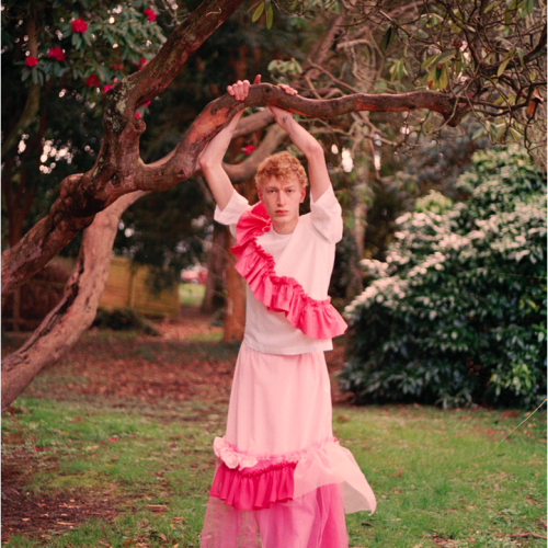 Male model in long and pink frilly dress holding tree branch in garden.