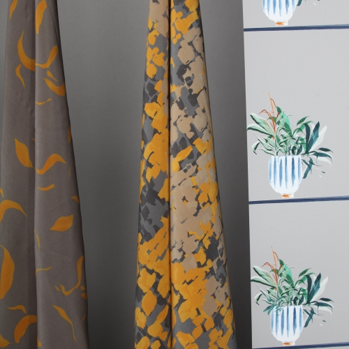 Grey and yellow fabrics and wallpaper with a green plant design.