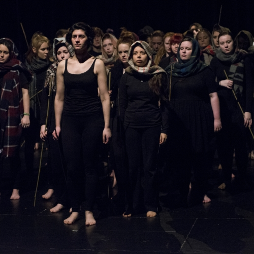 Group of students in dark clothes, head scarves and holding sticks on stage.