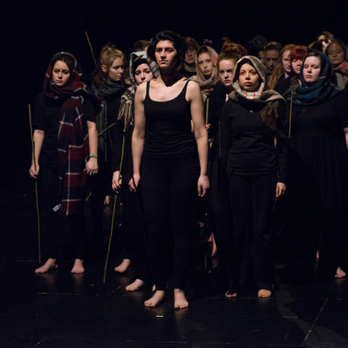 A group of Falmouth Acting students wearing black clothing and holding sticks