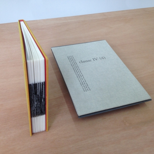 Hand bound book stood upright and grey cloth rectangle with type laid next to it.