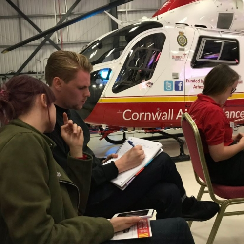 Students taking notes on chairs next to air ambulance.