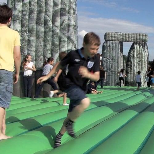 children running on an inflatable model of Stone Henge