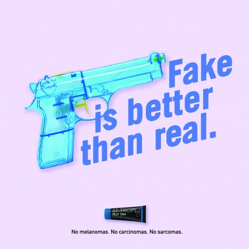 Blue toy gun with the text 'Fake is better than real'