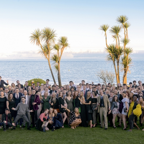Group of Journalism students stood in front of the sea with palm trees at an event.