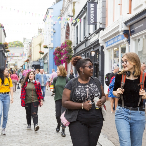 Group of students walking through Falmouth high street.