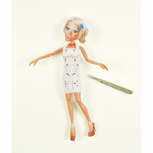 Barbie doll with cut out face from magazine, markings on body for surgery and scalpel next to it.