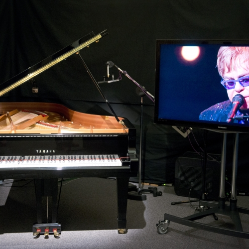 A piano with a red tape across the keys next to a screen with Elton John singing.