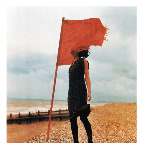 A fashion model wearing black clothes on a beach with a red flag