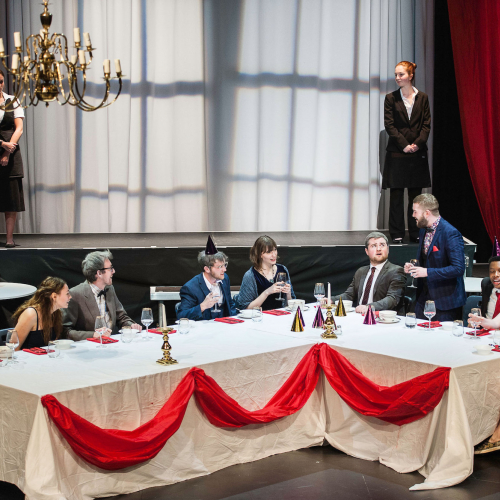 Student actors sat around a grand dining table and chandelier on stage