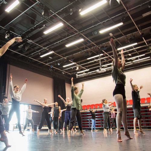 Falmouth University dance students raising their arms in a dance studio