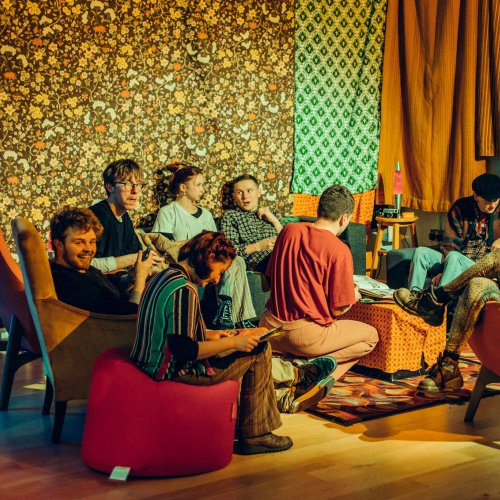 Falmouth University students sat in orange room with patterned seventies fabric.