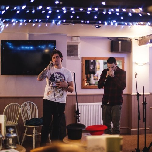 Two students on stage at a poetry slam, blue fairy lights on the ceiling