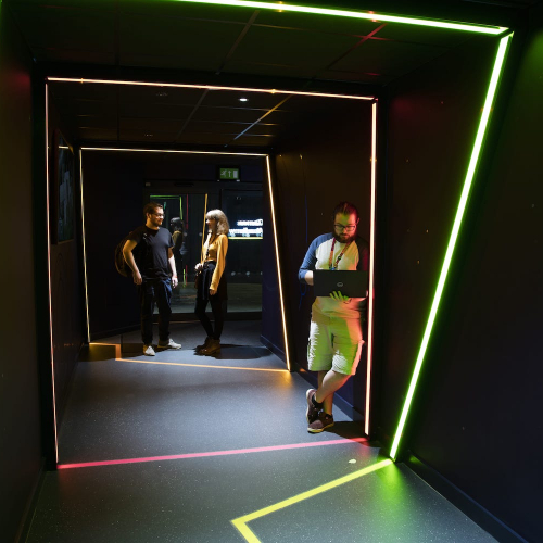 A dark room with lights and students from the Games Academy