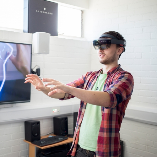 Student wearing virtual reality headset with arms extended in front and images of hands and electricity bolts on screen next to him.