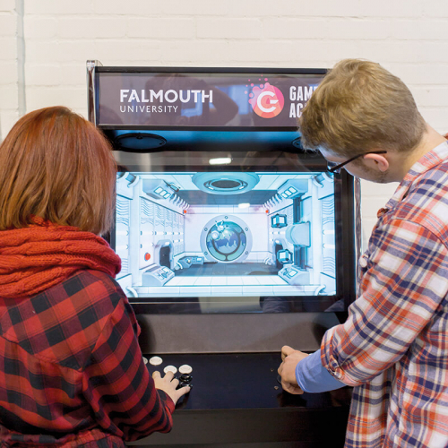 Two Falmouth University students playing on a retro games machine