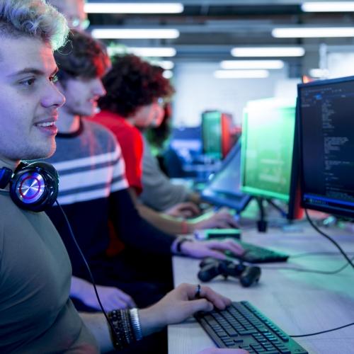 Student with headphones around neck working at computer in games studio.