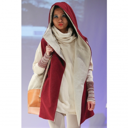 Model in red and cream hooded gilet and bag over shoulder,