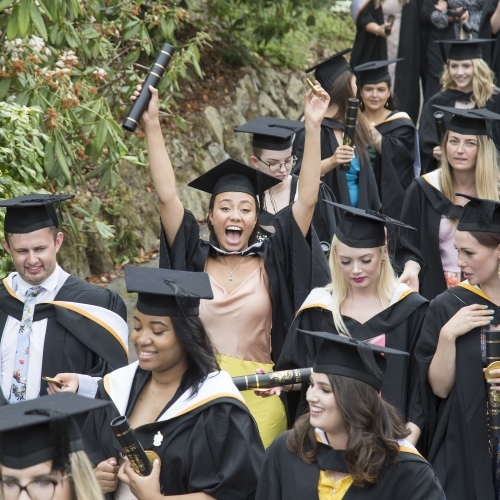 Falmouth University graduation 2019 – graduates walking through gardens in gowns and hats.