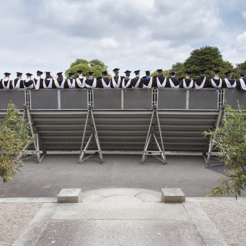 Rear view of Falmouth university graduates standing in stalls for group photographs at graduation 2019
