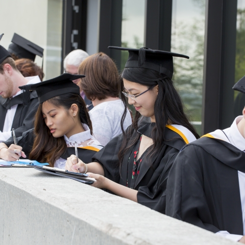 Graduates signing year books at Falmouth university Graduation 2019