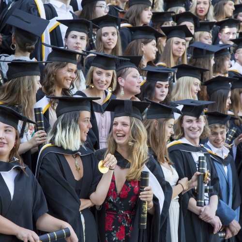 Graduates talking and laughing while posing for group photograph at graduation 2019