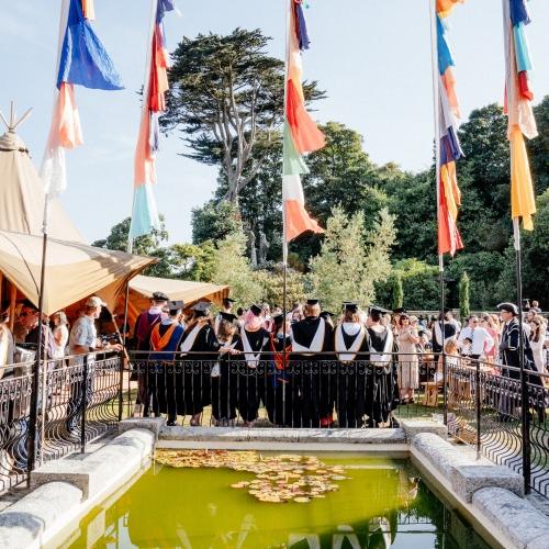 Guests gathered around a pond enjoying graduation 2019