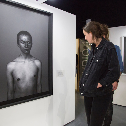 Woman looking at a framed photography portrait of a topless boy on a gallery wall.