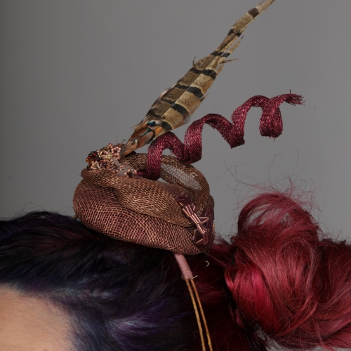 Stitched hair piece with feather and red spiral.