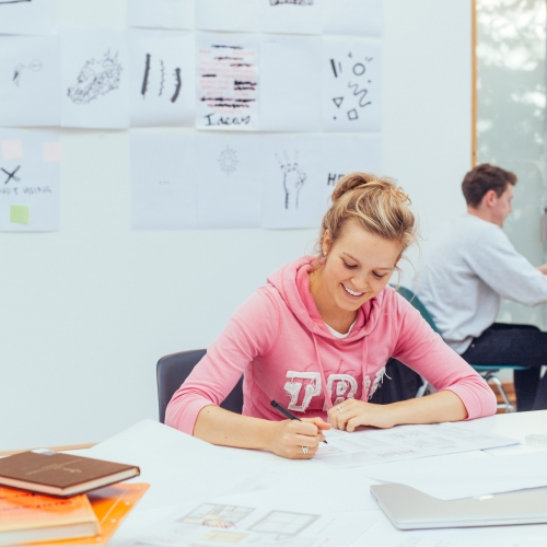 Female student in a pink hoodie seated at Falmouth University