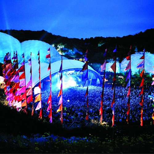 A gig at Eden Project at night surrounded by colourful silk flags.